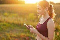 Corredor femenino que disfruta de la atmósfera tranquila mientras que activa en el campo, escuchando su pista preferida en auricu Foto de archivo
