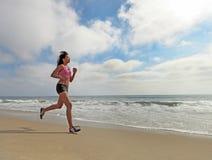 Corredor femenino que se ejecuta en la playa que activa Imagenes de archivo
