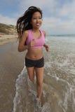 Corredor femenino que se ejecuta en la playa que activa Foto de archivo