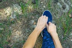 Corredor joven de la mujer de la aptitud que ata el cordón en rastro del bosque fotografía de archivo