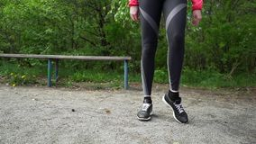 Corredor joven de la mujer de la aptitud que estira las piernas antes de funcionamiento almacen de video