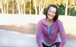 Corredor maduro de la mujer que toma un resto después de correr en el parque imagen de archivo libre de regalías