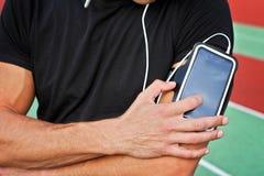 Corredor masculino com o telefone esperto móvel, escutando a música durante o exercício Correndo, movimentar-se, cardio-, esporte Fotografia de Stock Royalty Free