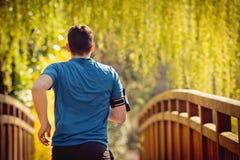 Corredor masculino de la vista posterior que corre en un parque de la ciudad sobre el puente foto de archivo libre de regalías
