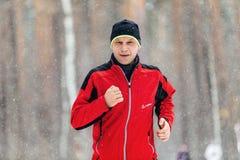 Corredor masculino do close up que corre na neve de queda na floresta Fotografia de Stock Royalty Free