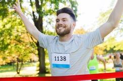 Corredor masculino joven feliz que gana en final de la raza Fotografía de archivo libre de regalías