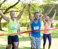 Corredor masculino joven feliz que gana en final de la raza Foto de archivo