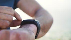 Corredor masculino joven que ajusta el smartwatch metrajes