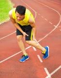 Corredor masculino joven que sufre del calambre de pierna en la pista fotos de archivo