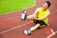 Corredor masculino joven que sufre del calambre de pierna en la pista Fotografía de archivo libre de regalías