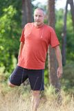Corredor masculino maduro del atleta que estira en bosque Imagen de archivo
