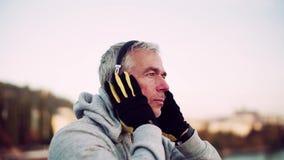 Corredor masculino maduro que pone en los auriculares al aire libre en ciudad almacen de video