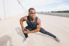 Corredor masculino no sportswear preto que estica os pés antes de fazer o exercício da manhã imagem de stock