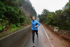Corredor masculino que activa y que corre en el camino en naturaleza imagenes de archivo