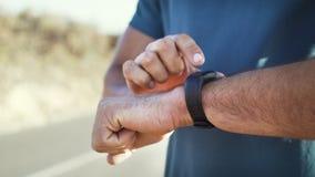 Corredor masculino que comprueba el reloj elegante almacen de video