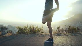 Corredor masculino que estira su pierna delante del sol naciente almacen de metraje de vídeo