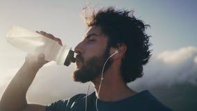 Corredor masculino sediento que bebe el agua de la botella metrajes