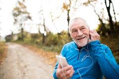Corredor mayor en naturaleza con el teléfono elegante con los auriculares Foto de archivo