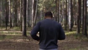 Corredor muscular que corre en el camino con la opinión de la parte posterior del bosque Hombre atlético que corre en el camino a almacen de metraje de vídeo