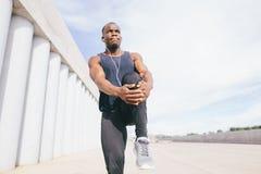 Corredor no sportswear preto que estica os pés antes de fazer o exercício da manhã fotografia de stock royalty free