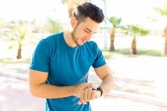Corredor que comprueba el corazón Rate On Smartwatch After Jogging en parque fotografía de archivo libre de regalías