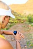 Corredor que comprueba el reloj de los deportes en montañas del verano en rastro imagen de archivo libre de regalías