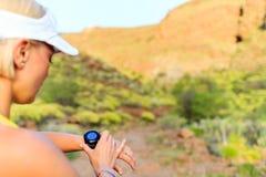 Corredor que comprueba el reloj de los deportes en montañas del verano en rastro foto de archivo libre de regalías