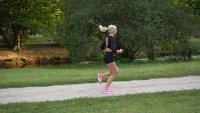 Corredor que corre en el parque, cámara lenta de la mujer almacen de video