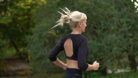 Corredor que corre no parque, movimento lento da mulher video estoque