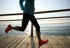 corredor que corre no passeio à beira mar do beira-mar durante o nascer do sol Fotografia de Stock Royalty Free