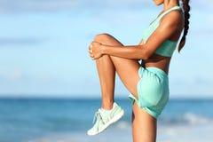 Corredor que estira la pierna durante calentamiento al aire libre en la playa antes de funcionamiento imagen de archivo
