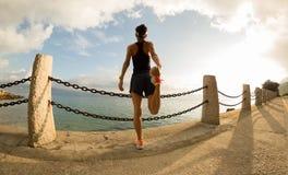 Corredor que estira las piernas antes de correr en la playa imagen de archivo