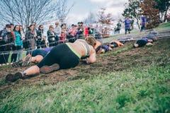 Corredor que rasteja sob o arame farpado em um teste da raça de obstáculo extrema Imagem de Stock Royalty Free