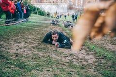 Corredor que se arrastra debajo del alambre de púas en una prueba de la raza de obstáculo extrema Fotografía de archivo