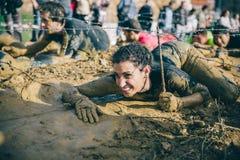 Corredor que se arrastra debajo del alambre de púas en una prueba de la raza de obstáculo extrema Foto de archivo