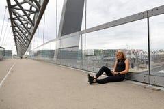 Corredor que se sienta en el puente después de entrenamiento y que usa el teléfono elegante fotos de archivo libres de regalías