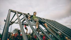 Corredor que va abajo de la estructura en una prueba de la raza de obstáculo extrema Foto de archivo libre de regalías