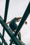 Corredor que va abajo de la pared en una prueba de la raza de obstáculo extrema Fotografía de archivo
