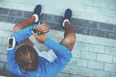 Corredor que verifica resultados usando o relógio esperto, sentando-se na rua após movimentar-se e descansando, fita com o telefo imagens de stock royalty free