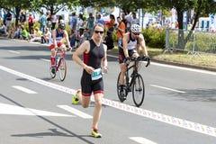 Corredor y ciclistas durante la primera raza de Szczecin del Triathlon Imagen de archivo libre de regalías