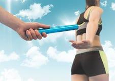 Corredor y mano de retransmisión con el bastón azul contra el cielo con las llamaradas fotografía de archivo