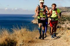 corredores de los atletas del grupo que corren el rastro a lo largo del mar Imagen de archivo libre de regalías