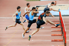 corredores de los hombres que corren la carrera en obstáculos de 110 metros Fotografía de archivo