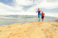 Corredores de los pares que corren con las mochilas en rastro del rocku en la playa Fotografía de archivo libre de regalías