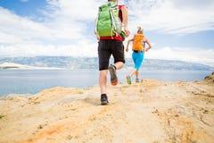 Corredores de los pares que corren con las mochilas en rastro del rocku en la playa Fotos de archivo