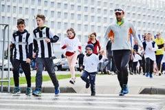 Corredores de maratón en los niños cruzados Imagen de archivo libre de regalías