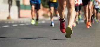 Corredores de maratona que correm na estrada de cidade Fotografia de Stock Royalty Free