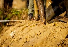 Corredores de raza del fango, derrotando obstáculos Detalles de las manos imagen de archivo