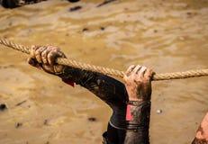 Corredores de raza del fango, derrotando obstáculos usando cuerdas Detalles de las manos imagen de archivo libre de regalías