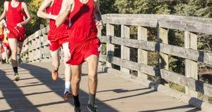 Corredores del campo a través de la High School secundaria de los muchachos que pasan un bridg de madera Foto de archivo